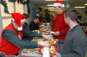 """VetChristmas02---Air Force Communications Agency volunteer, Joe DiGiovanni, and Airman 1st Class Randolph Finkbeiner, 375th Logistics Readiness Squadron volunteer, serves holiday dinner to the Veterans during the annual """"Christmas with the Vets"""" visit at the Quincy Illinois Veteran's Retirement Home.  Photo by Marv Lynchard"""